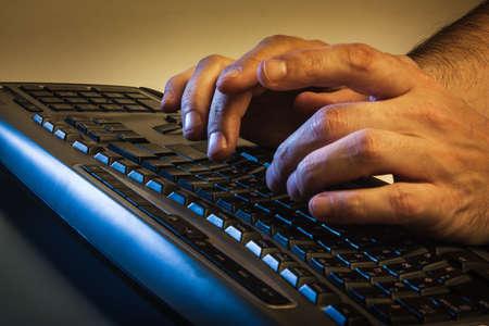teclado: Cierre de vista de ángulo bajo de un hombre escribiendo en un ordenador portátil en la oscuridad conceptual