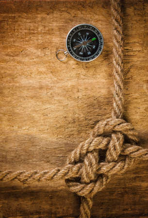 rope: Compass with a rope on the background of the old board Stock Photo