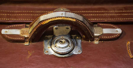 wornout: Front view of vintage worn-out leather suitcase with three metallic locks in retro style. Stock Photo