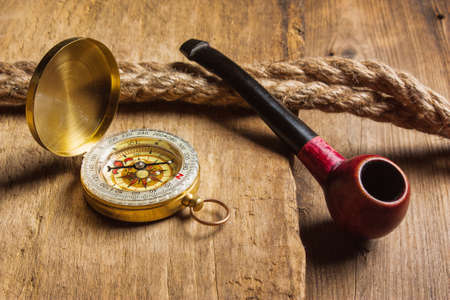 unexplored: Compass and a pipe with a rope on the background of the old board