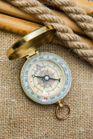 unexplored: Compass with a rope on the background of the old pattern