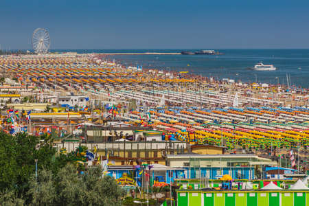 Rimini, ITALY - JUNE 24, 2014: Large group of parasols at the beach of Rimini, Itali Редакционное