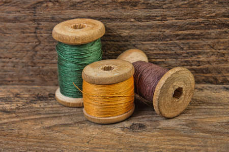 old spools: Spools of thread on a background of the old wooden planks Stock Photo