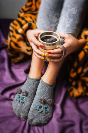 legwarmers: legs of girl in warm woolen socks and a cup of coffee warming, winter morning at home