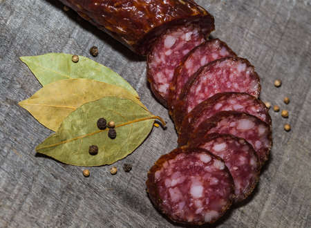 salame: sliced smoked sausage on the wood background with spices