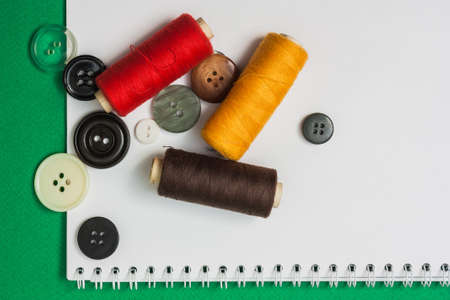 darn: thread with a needle and buttons on the background of the notebook Stock Photo