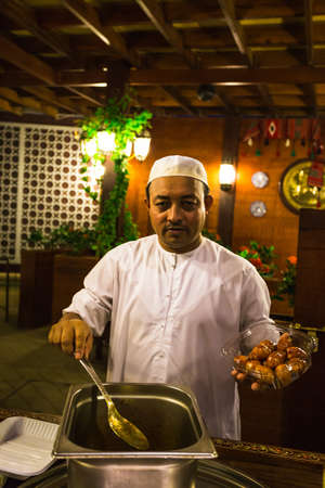 persian gulf: DUBAI, UAE - NOVEMBER 3: Street cafe in Dubai Marina. In the city of artificial channel length of 3 kilometers along the Persian Gulf. Chef bakes donuts Editorial