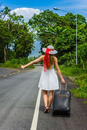 roadside stand: Girl with a suitcase on a deserted road in wild jungle