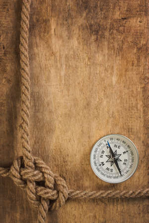 unexplored: Compass with a rope on the background of the old board Stock Photo