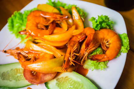 second breakfast: Shrimp with onions, lettuce, cucumber and sour sauce on a white plate Stock Photo
