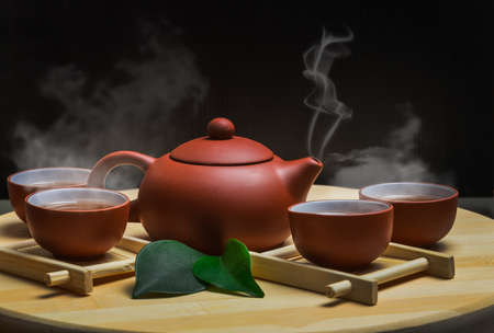 Teekanne und eine Tasse grüner Tee auf Holztisch