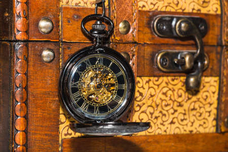accuracy: vintage pocket watch against the background of an old trunk