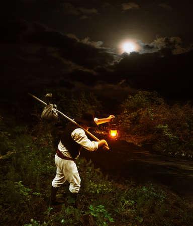 vestidos antiguos: viajero en ropa vieja con una mochila y una lámpara de queroseno en el cruce sobre el río