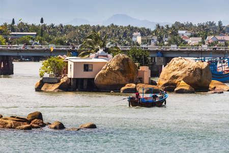 trang: Nha Trang, Vietnam, NOV, 11, 2014. Boats and rocks near fishing village on the river Kai in Nha Trang