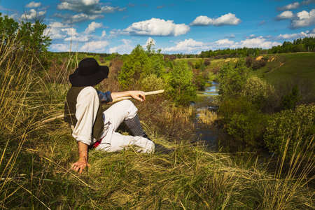 man in a black hat sits on a hill near the river Stock Photo