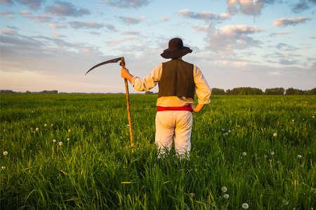 vestidos antiguos: hombre en ropa vieja siega la hierba en el campo Foto de archivo
