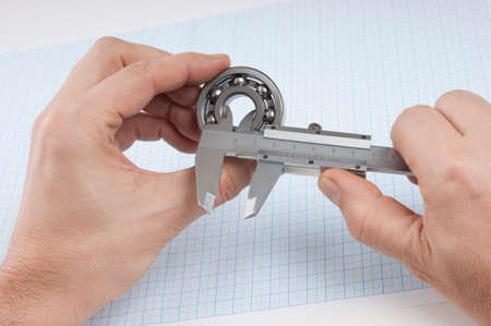 calipers: calipers, bearing and square on the background of graph paper