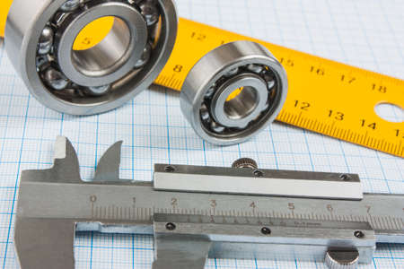 chock: calipers, bearing and square on the background of graph paper
