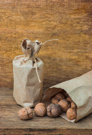 background texture metaphor: Walnuts in paper bags on the background of an old wooden board Stock Photo