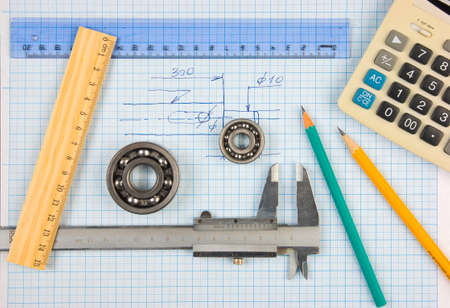 calipers, bearing and square on the background of graph paper