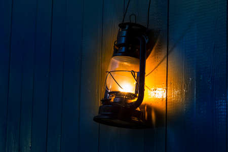 The old kerosene lantern hanging on the yellow wooden wall Stock Photo