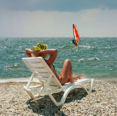sailboard: girl on the white chaise lounge on the beach in sunny day