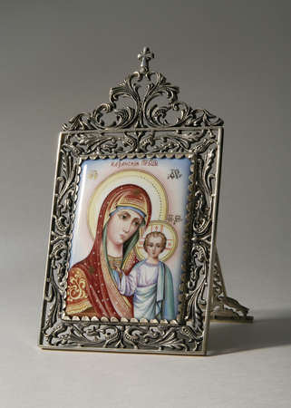 Ancient Russian icon on ceramics in silver frame. Mother of God (Mary) and child (Jesus Christ)