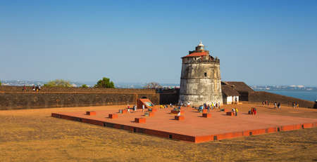aguada: CANDOLIM, GOA, INDIA - 4 MARCH 2017: Ancient Fort Aguada and lighthouse built in the 17th century. Popular place for tourists in Goa, India. Located near the popular resorts of Candolim and Calangute