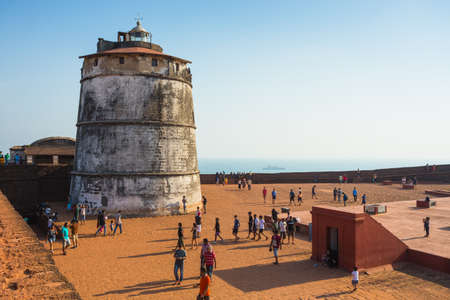aguada: CANDOLIM, GOA, INDIA - 4 MARCH 2017: Ancient Fort Aguada and lighthouse built in the 17th century. A popular place for tourists in Goa, India. Located near the popular resorts of Candolim and Calangute