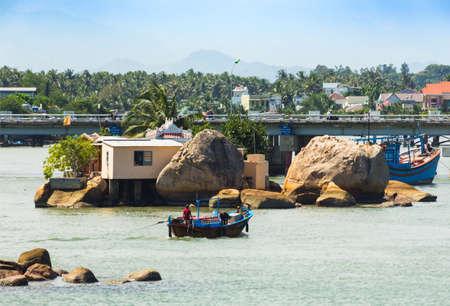 Nha Trang, Vietnam, NOV, 11, 2014. Boats and rocks near fishing village on the river Kai in Nha Trang