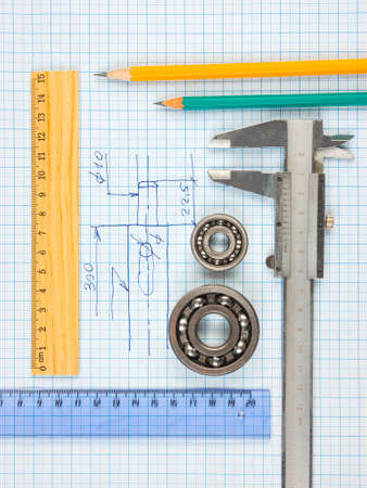 calipers, bearing and square on the background of graph paper Stock Photo - 105620349