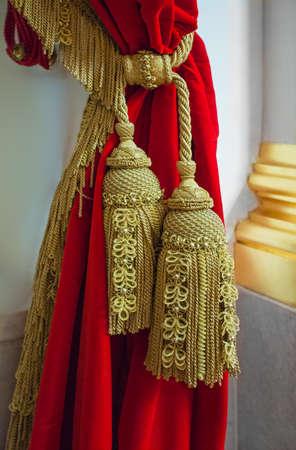 Brosses et franges dorées sur le rideau rouge Banque d'images