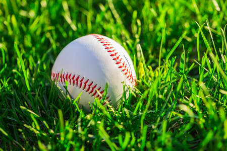 Close up side of baseball ball on grass field