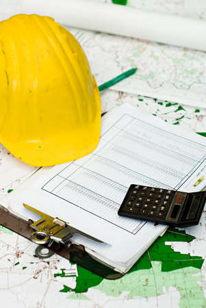 estimate: Objects representing the financial aspect of construction - a yellow hardhat, clipboard with a table of figures, a pen, and a calculator - all sitting on top of area plans.