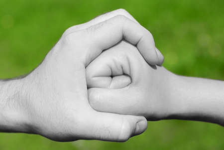 anger management: black and white hand holding or stopping a fist in frot of green background Stock Photo