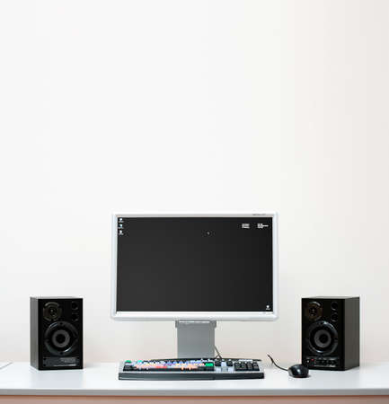 Computer system setup with speakers, monitor for video editing on a white desk photo