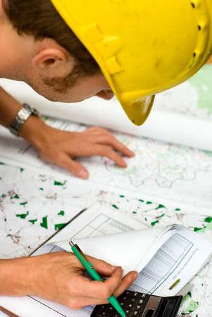 revisando documentos: trabajador de la construcción el cálculo y control de documentos, mapas y gráficos