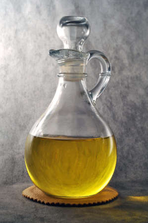 Glass bottle of olive oil isolated on a gray background Stock Photo - 17921913