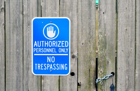 An Authorized Personnel Only No Trespassing sign on a chained old wooden fence   photo