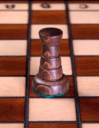Rook chess piece made of wood, on a wooden chess board   Stock Photo - 23023315