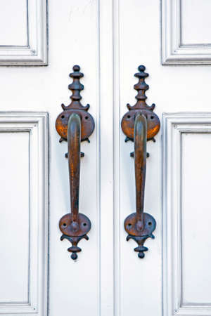 White doors and handles of an entrance to a new church