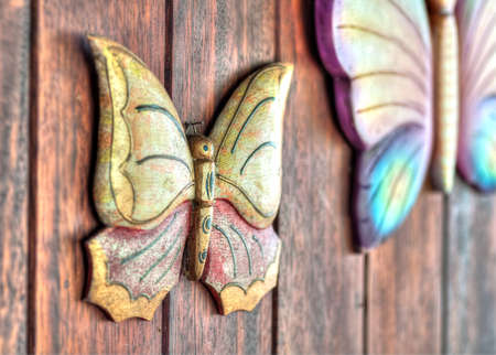 wood figurine: A butterfly figurine made of wood hanging from a wall Stock Photo