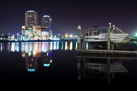 iluminated: Barcos en un embarcadero en nocturno con edificios iluminados en el fondo Editorial