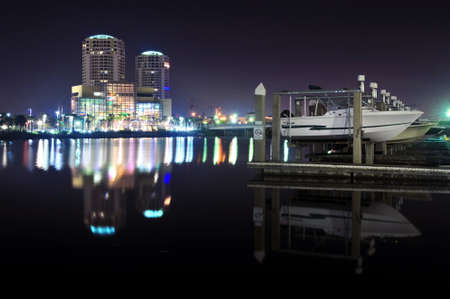 nightime: Boats at a pier at nightime with iluminated buildings in the background Editorial