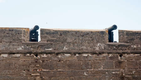 16th century: Pair of old canons behind the fort walls, aiming at the sea, on an overcast day. Castillo de San Marcos, St. Augustine, Florida. 16th century.