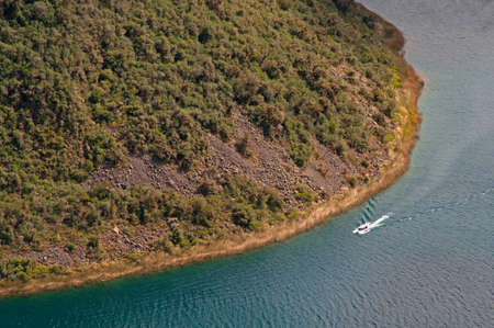 navigating: A tourist boat navigating around one of the center islands at the volcanic crater and lake of Cuicocha