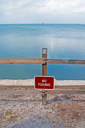 trespass: A No Fishing sign in the sand in front of the ocean, on a sunny afternoon, Florida, USA Stock Photo