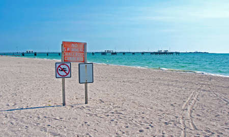 restricted area: No Swimming Dangerous Currents sign, stuck in the sand on a beautiful Florida beach, late afternoon.