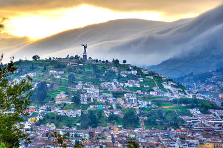 View of the Panecillo hill with the Virgen Mary statue, with houses and rooftops of downtown Quito, Pichincha, Ecuador, at sunset.