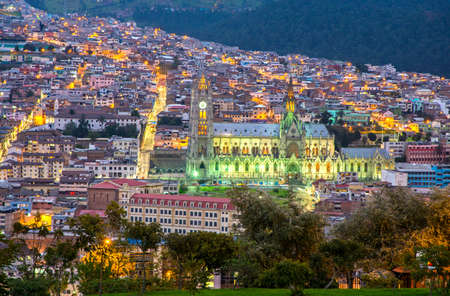 Side view of the Basilica of Quito at sunset, with its neighboring houses, buildings and rooftops of the historic and old downtown area. Quito, Pichincha, Ecuador. Фото со стока